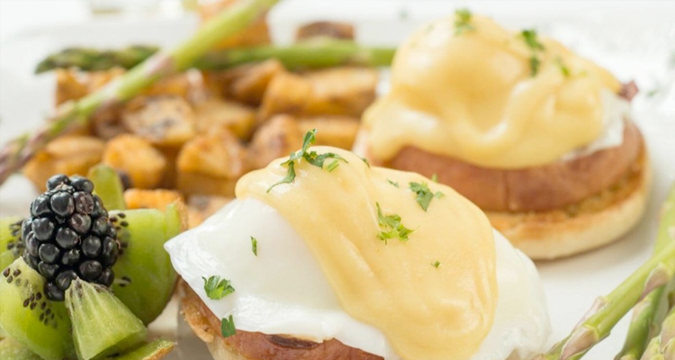 Breakfast plate with Eggs Benedict, potatoes and fruit
