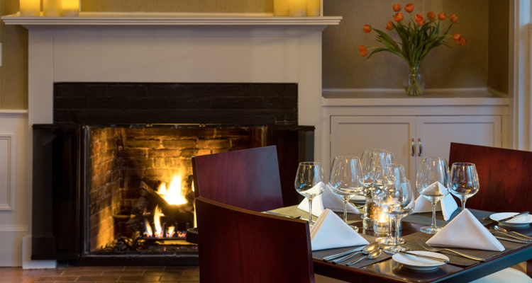 Cozy restaurant table set with wine glasses in front of a roaring fire in the fireplace