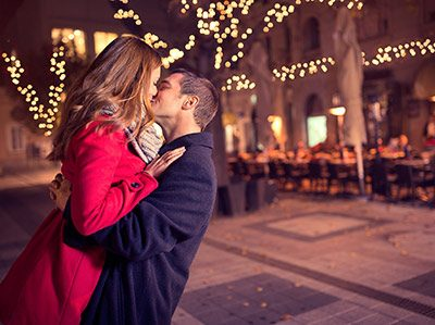Couple kissing in front of Christmas lights