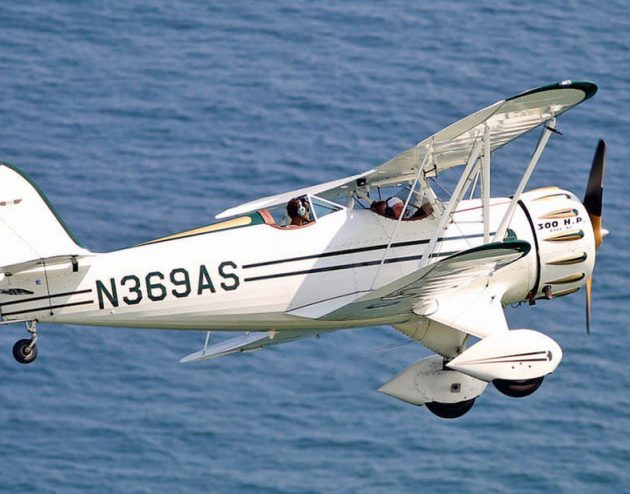 Biplane flying over the Ocean