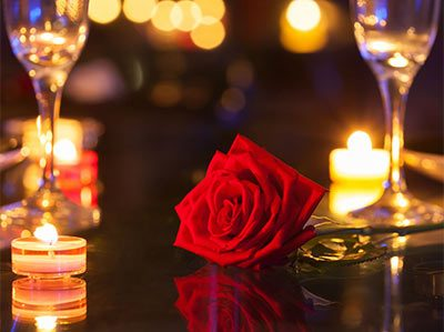 Single red rose with wine glasses and candles