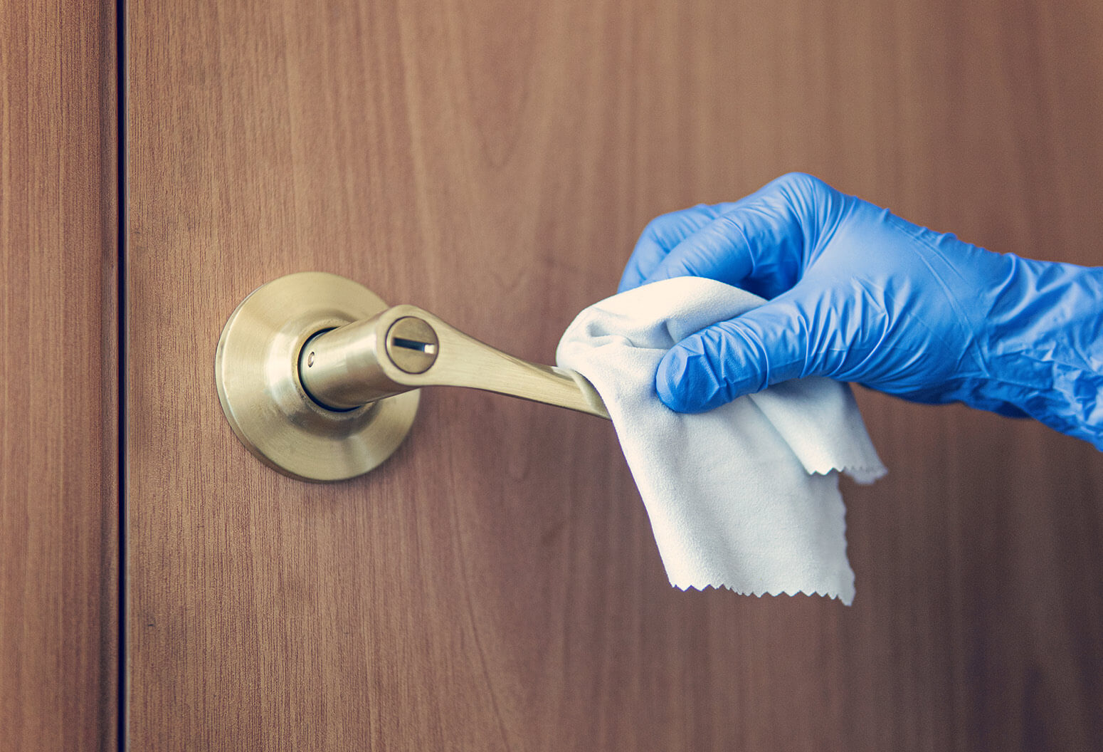 gloved hand cleaning a door handle